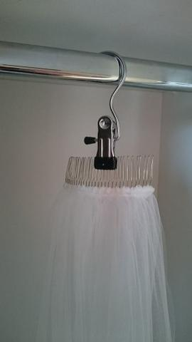 Bridal veil hanging up in closet with a bridal veil storage clip