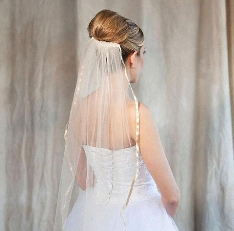 Bride wearing a 1 tier beige colored fingertip length bridal veil made of illusions bridal tulle
