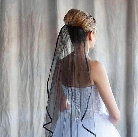 Bride wearing a 1 tier black fingertip length veil with ribbon edge