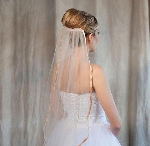 Bride wearing a 1 tier cafe colored bridal veil with ribbon edge