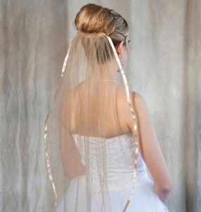 Bride wearing a 1 tier gold colored fingertip length veil with ribbon edge