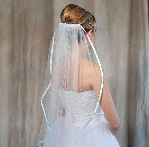 Bride wearing 1 tier light blue colored bridal veil made from bridal illusion tulle
