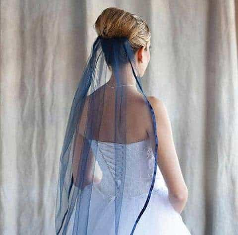 Bride wearing a 1 tier navy blue finger tip bridal veil with ribbon edge