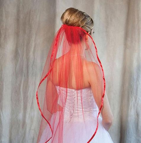 Bride wearing a 1 tier red colored fingertip length bridal veil with ribbon edge