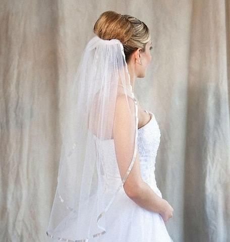 Bride wearing a 1 tier silver colored fingertip length veil with ribbon edge