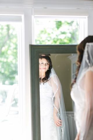 Bride looking in the mirror wearing a 1 tier bridal veil with thin delicate lace edge
