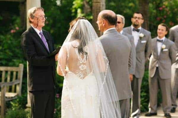 Bride walking down the aisle with father wearing a chapel length veil with lace edging