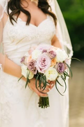 Bride wearing lace veil holding a bouquet with purple, white and peach flowers