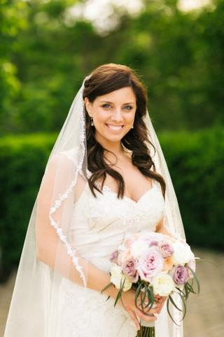 bride holding a bridal bouquet with purple and white flowers wearing a bridal veil with thin lace edge
