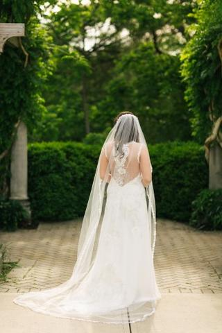 Bride wearing a custom made chapel length veil with a thin lace edge