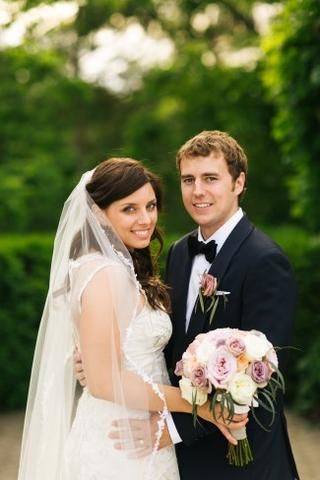 bride and groom posing together with bride holding her bouquet and lace edge bridal veil