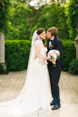 Groom kissing bride who is wearing a long bridal veil with lace edge