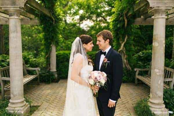 bride and groom portrait with bride wearing a chapel length veil with delicate lace edging