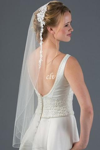 Bride wearing a 1 tier fingertip length veil with a lace mantilla style