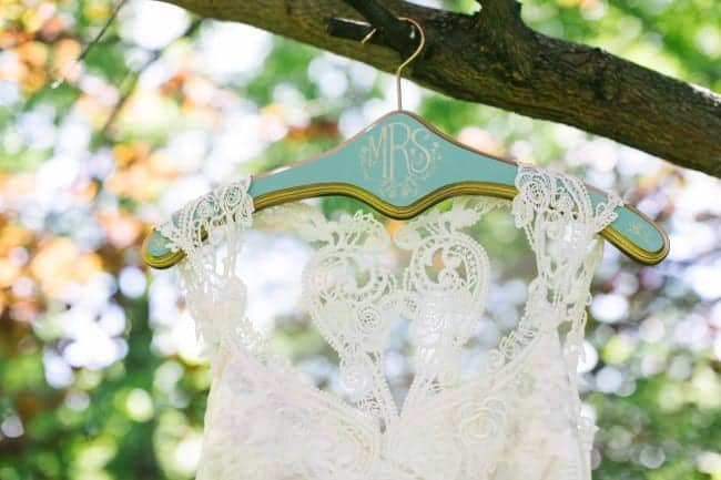 Beautiful Lace wedding dress hanging from a tree on a personalized turquoise hanger
