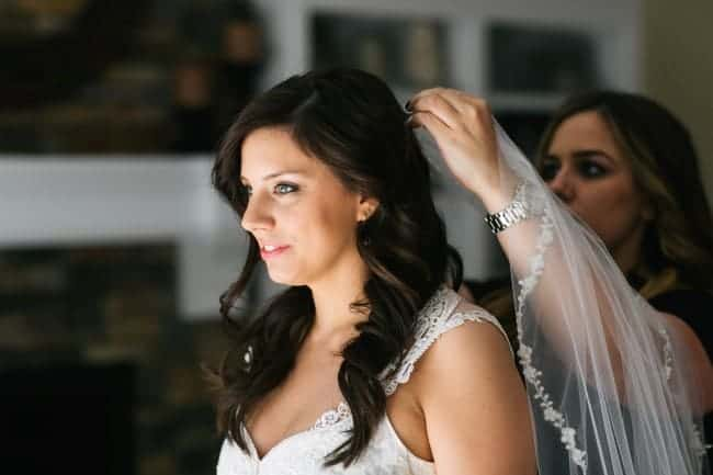 Mother of the bride placing a custom made 1 tier chapel length veil in bride's hair