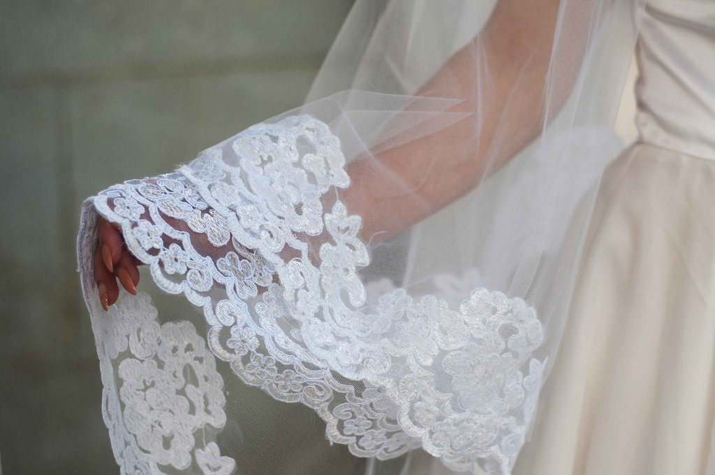 Bride wearing a drop knee length veil with thick white lace