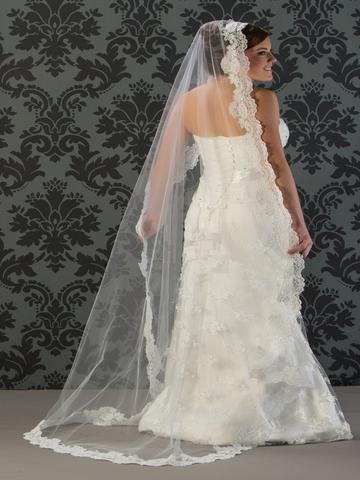 Bride wearing a 1 tier chapel length bridal veil in a mantilla style with thick lace edge