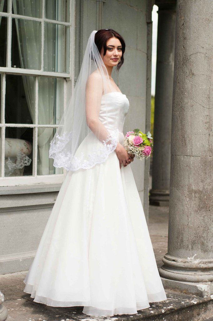 Bride wearing a 1 tier fingertip length veil with lace around the bottom edge