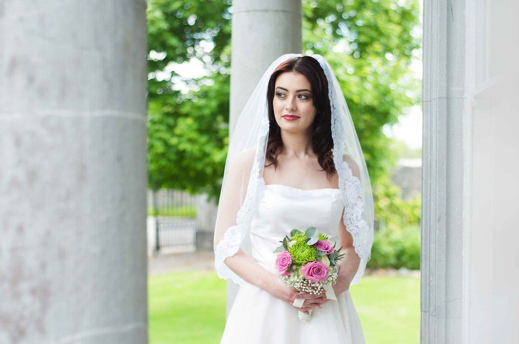Bride wearing a 1 tier waist length veil with thick lace edge