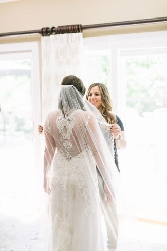 Hair stylist fixing bride's 1 tier chapel length veil with thin lace edging